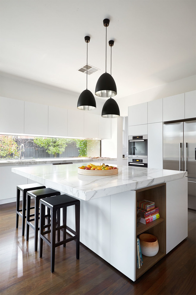 Kitchen - mid-sized contemporary dark wood floor kitchen idea in Melbourne with flat-panel cabinets, white cabinets, marble countertops, white backsplash, stainless steel appliances and an island