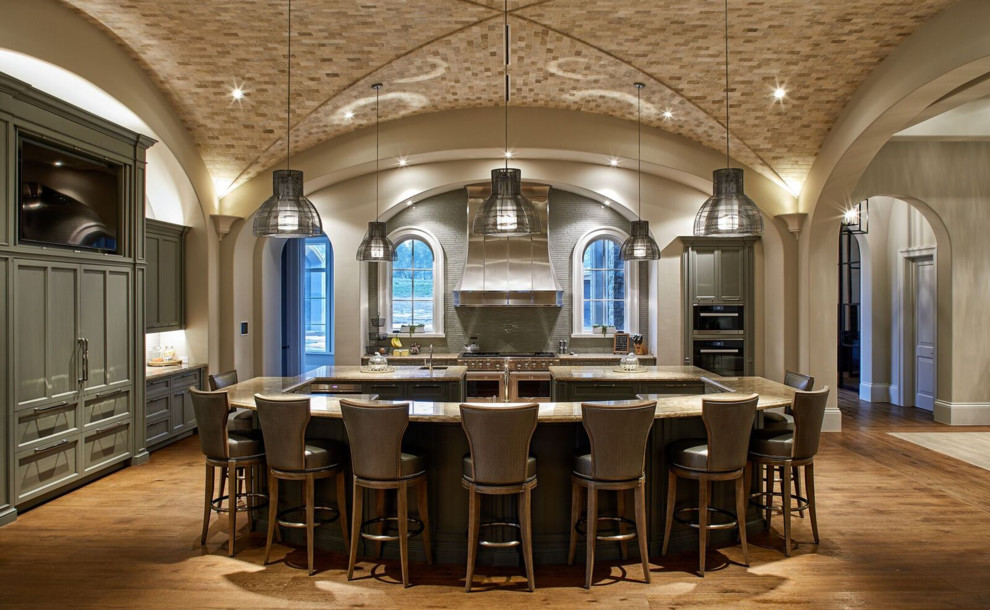 Kitchen - traditional l-shaped medium tone wood floor and brown floor kitchen idea in Houston with an undermount sink, recessed-panel cabinets, green cabinets, gray backsplash, black appliances, two islands and beige countertops