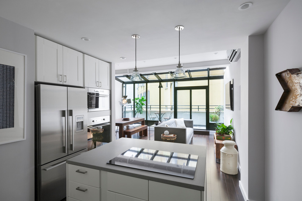 Example of a mid-sized minimalist single-wall dark wood floor and brown floor open concept kitchen design in New York with white cabinets, stainless steel appliances, shaker cabinets, concrete countertops and an island