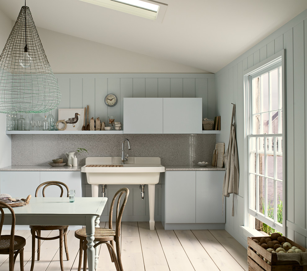 Example of a mid-sized coastal single-wall light wood floor and beige floor eat-in kitchen design in Milwaukee with a farmhouse sink, flat-panel cabinets, blue cabinets, quartz countertops, gray backsplash, stone slab backsplash and no island