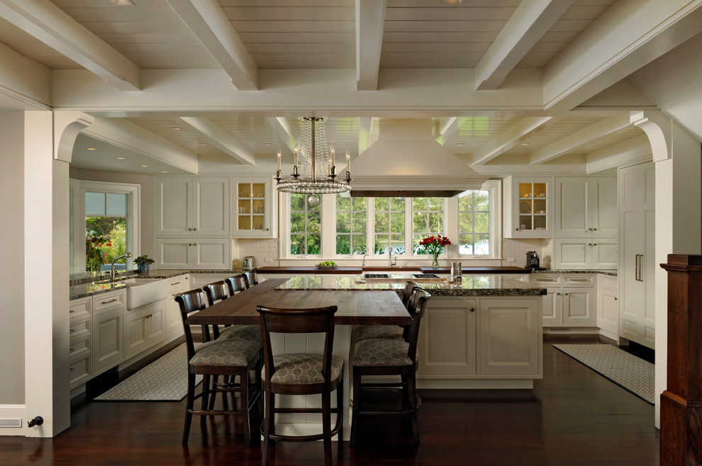 Inspiration for a large timeless u-shaped dark wood floor eat-in kitchen remodel in Baltimore with white cabinets, granite countertops, white backsplash, subway tile backsplash, an island, recessed-panel cabinets, paneled appliances and a farmhouse sink