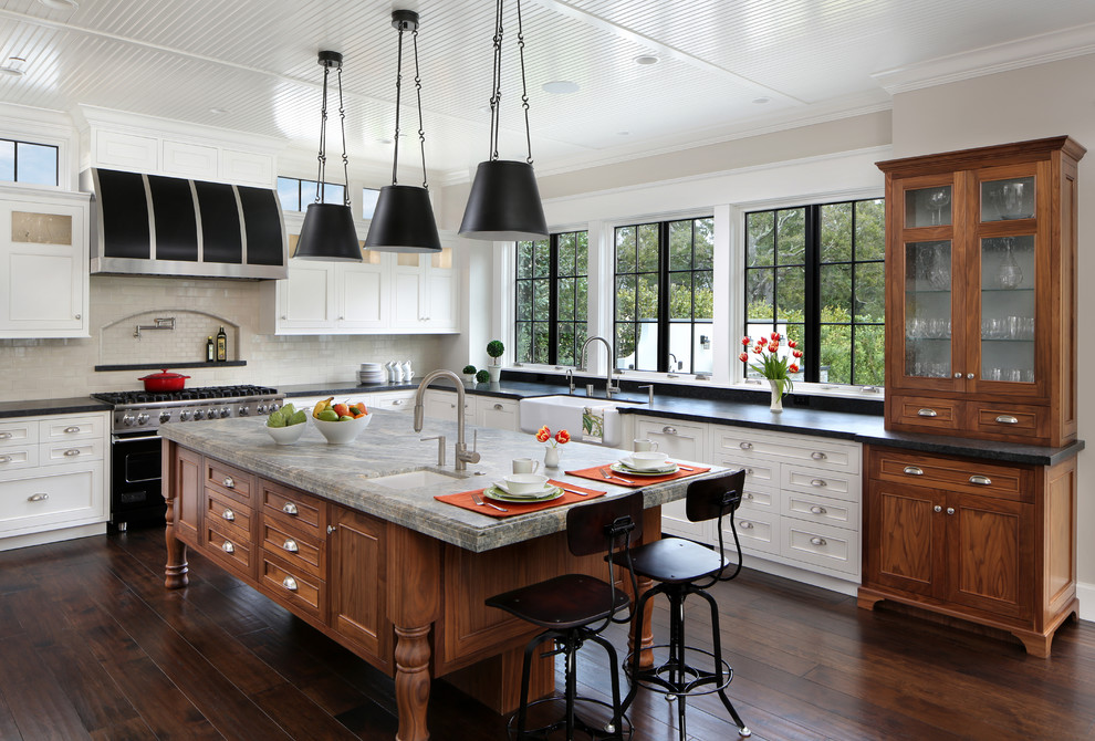 Inspiration for a large timeless l-shaped dark wood floor and brown floor open concept kitchen remodel in San Francisco with a farmhouse sink, recessed-panel cabinets, white cabinets, white backsplash, black appliances, an island, granite countertops and subway tile backsplash