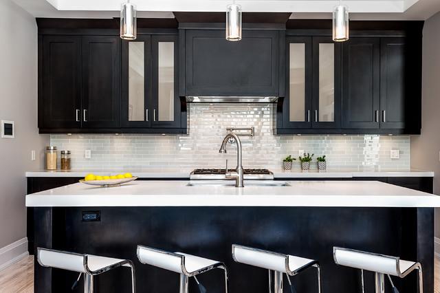 Bild på ett vintage kök, med en undermonterad diskho, luckor med glaspanel, svarta skåp, grått stänkskydd, stänkskydd i tunnelbanekakel och ljust trägolv
