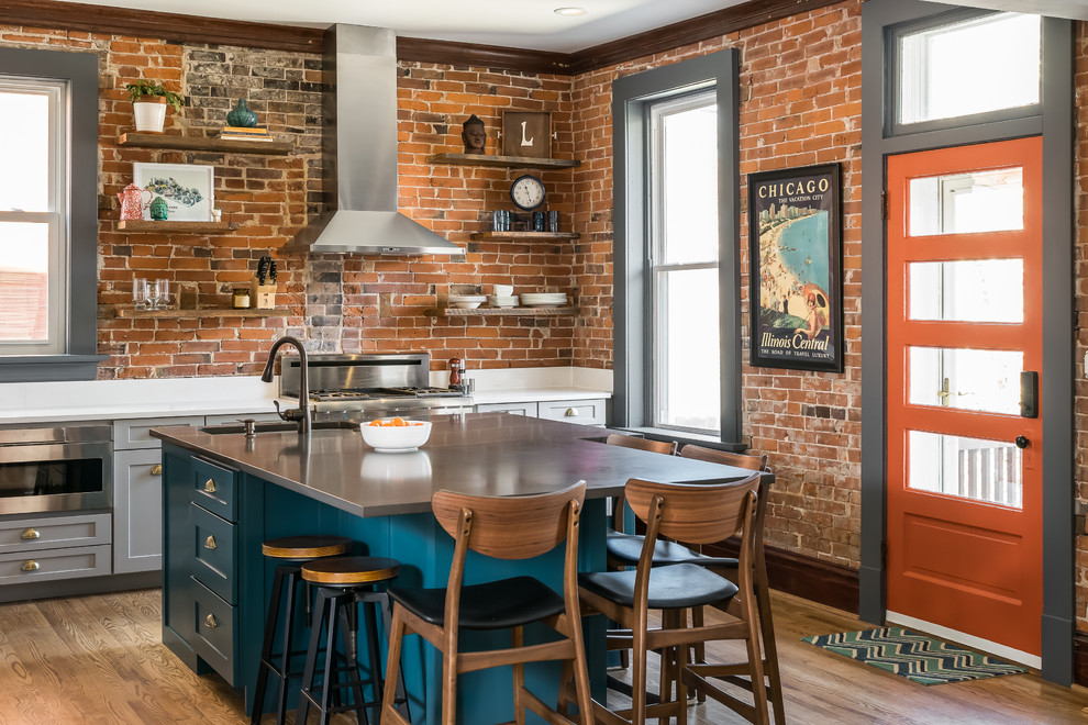 Mid-sized eclectic medium tone wood floor kitchen photo in St Louis with a single-bowl sink, shaker cabinets, gray cabinets, quartz countertops, brick backsplash, stainless steel appliances, an island and white countertops