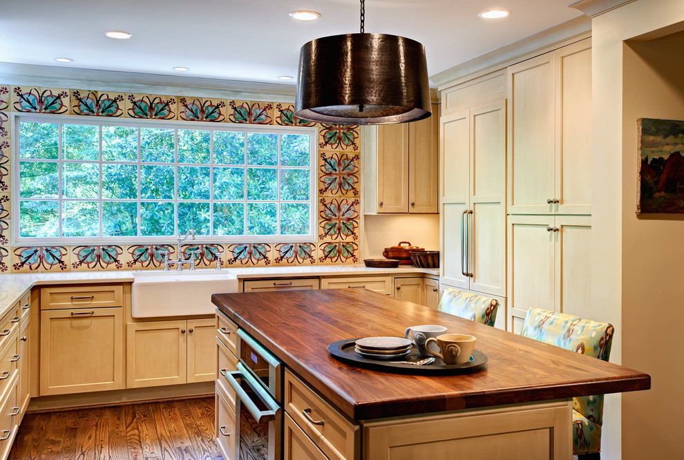 Elegant kitchen photo in Charlotte with a farmhouse sink, wood countertops, shaker cabinets, multicolored backsplash and paneled appliances