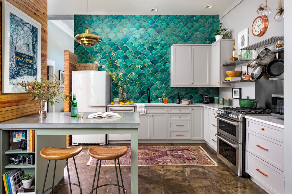 Eclectic l-shaped concrete floor and brown floor kitchen photo in Atlanta with an undermount sink, shaker cabinets, gray cabinets, quartz countertops, green backsplash, ceramic backsplash, stainless steel appliances, white countertops and a peninsula