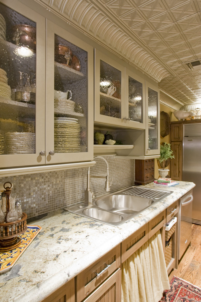 Inspiration for a timeless kitchen remodel in Phoenix with a drop-in sink, glass-front cabinets, gray cabinets, gray backsplash, mosaic tile backsplash, stainless steel appliances and granite countertops