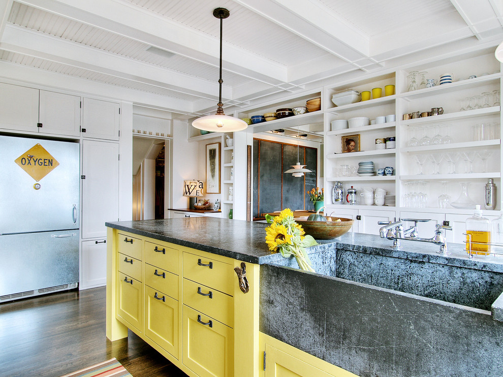 Example of an eclectic kitchen design in Seattle with stainless steel appliances, an integrated sink, open cabinets, yellow cabinets and soapstone countertops