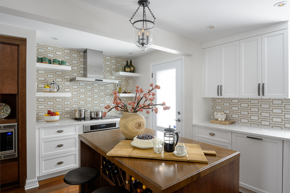 Mid-sized transitional l-shaped dark wood floor and brown floor open concept kitchen photo in Ottawa with wood countertops, white cabinets, multicolored backsplash, stainless steel appliances, recessed-panel cabinets, mosaic tile backsplash and an island