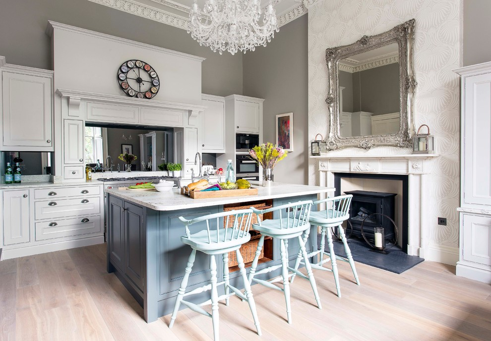 Eclectic light wood floor kitchen photo in Edinburgh with recessed-panel cabinets, white cabinets, mirror backsplash and an island