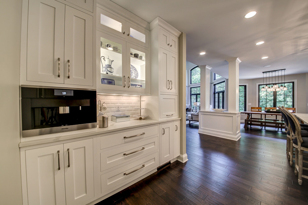 Example of a large transitional l-shaped dark wood floor and brown floor eat-in kitchen design in Dallas with an undermount sink, shaker cabinets, white cabinets, marble countertops, white backsplash, ceramic backsplash, paneled appliances, an island and white countertops
