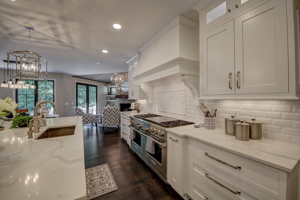 Inspiration for a large transitional l-shaped dark wood floor and brown floor eat-in kitchen remodel in Dallas with an undermount sink, shaker cabinets, white cabinets, marble countertops, white backsplash, ceramic backsplash, paneled appliances, an island and white countertops
