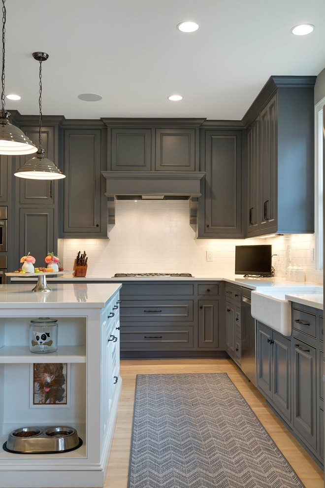 Inspiration for a large farmhouse l-shaped light wood floor and beige floor open concept kitchen remodel in Minneapolis with a farmhouse sink, shaker cabinets, gray cabinets, solid surface countertops, white backsplash, subway tile backsplash, stainless steel appliances and an island