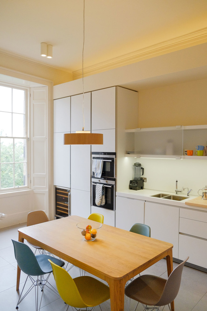 Inspiration for a scandinavian eat-in kitchen remodel in Edinburgh with an undermount sink, flat-panel cabinets, white cabinets and white backsplash