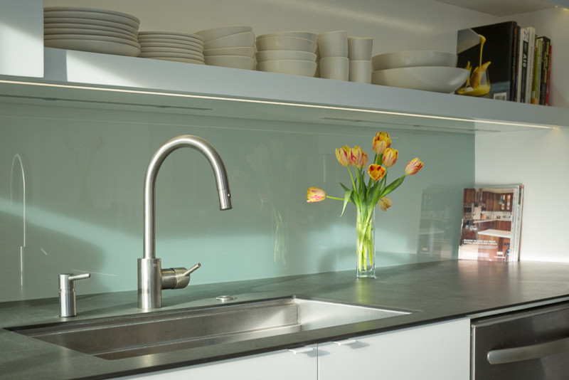 Example of a mid-century modern galley eat-in kitchen design in San Francisco with an undermount sink, flat-panel cabinets, white cabinets, white backsplash, glass sheet backsplash and stainless steel appliances