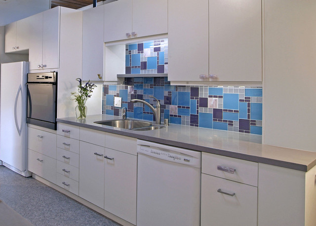 Example of a trendy kitchen design in Omaha with a double-bowl sink, white appliances, flat-panel cabinets, white cabinets, multicolored backsplash and glass tile backsplash