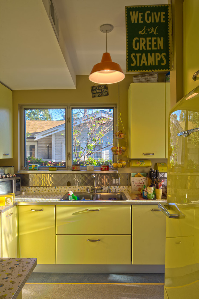 Kitchen - eclectic kitchen idea in Los Angeles with yellow cabinets, metallic backsplash and metal backsplash