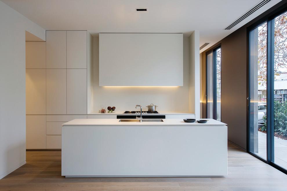 Kitchen - mid-sized modern galley medium tone wood floor kitchen idea in Melbourne with an undermount sink, flat-panel cabinets, white cabinets, white backsplash, an island and glass sheet backsplash