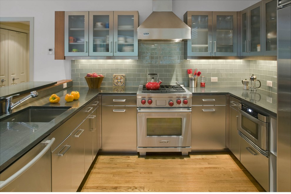 Inspiration for a contemporary u-shaped kitchen remodel in New York with subway tile backsplash, a single-bowl sink, flat-panel cabinets, gray backsplash, stainless steel appliances and stainless steel cabinets