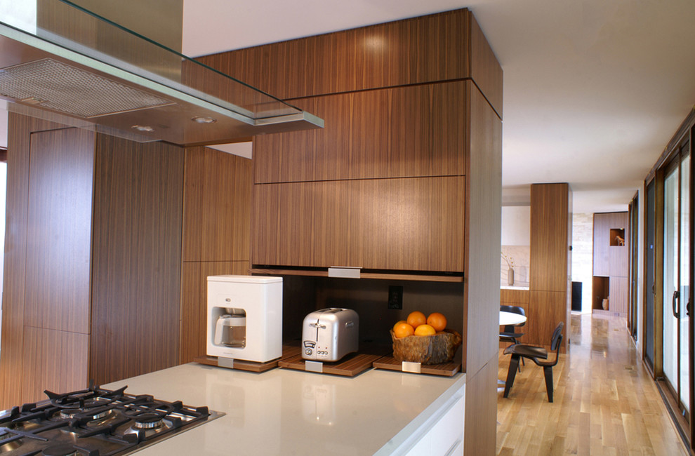 Large minimalist l-shaped light wood floor eat-in kitchen photo in San Francisco with flat-panel cabinets, medium tone wood cabinets, marble countertops and a peninsula