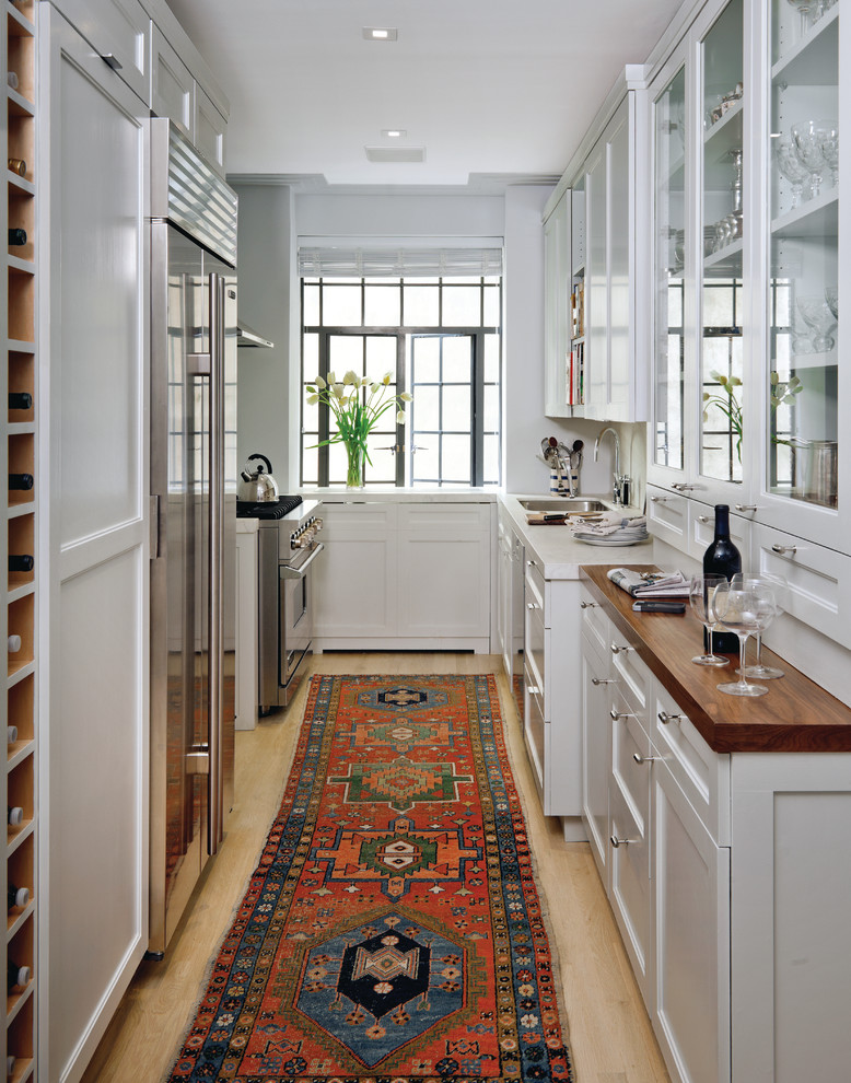 Transitional u-shaped enclosed kitchen photo in New York with stainless steel appliances, glass-front cabinets, white cabinets and an undermount sink