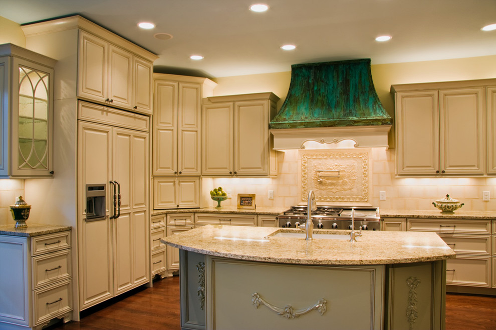 Example of a classic kitchen design in Austin with raised-panel cabinets, an undermount sink, beige cabinets, granite countertops and beige backsplash
