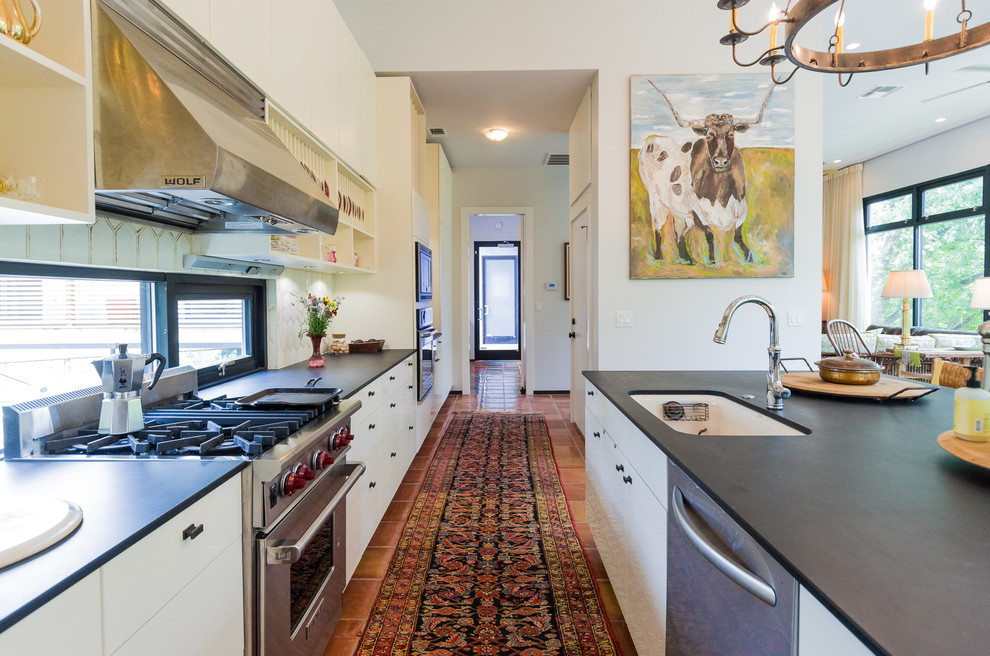 Transitional kitchen photo in Austin with flat-panel cabinets, white cabinets, white backsplash and stainless steel appliances