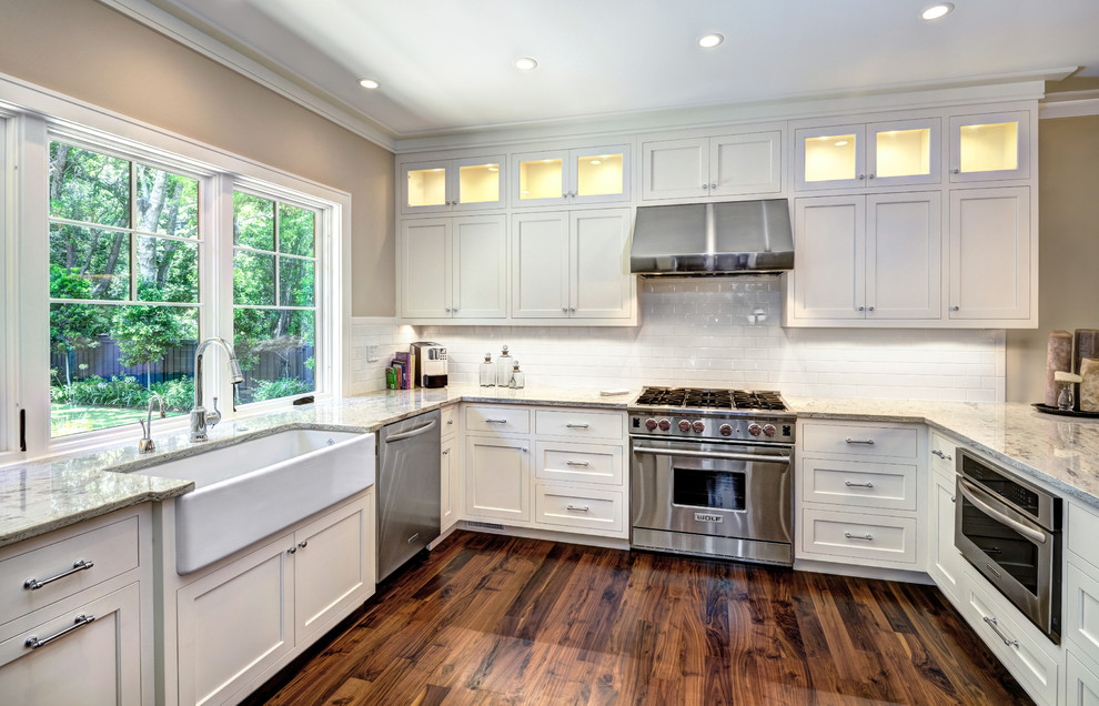 Inspiration for a mid-sized transitional u-shaped eat-in kitchen remodel in Charleston with a farmhouse sink, shaker cabinets, white cabinets, white backsplash, subway tile backsplash, stainless steel appliances and an island