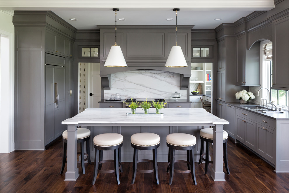 Example of a transitional u-shaped dark wood floor and brown floor eat-in kitchen design in Minneapolis with an undermount sink, recessed-panel cabinets, gray cabinets, white backsplash, stone slab backsplash, paneled appliances, an island and white countertops