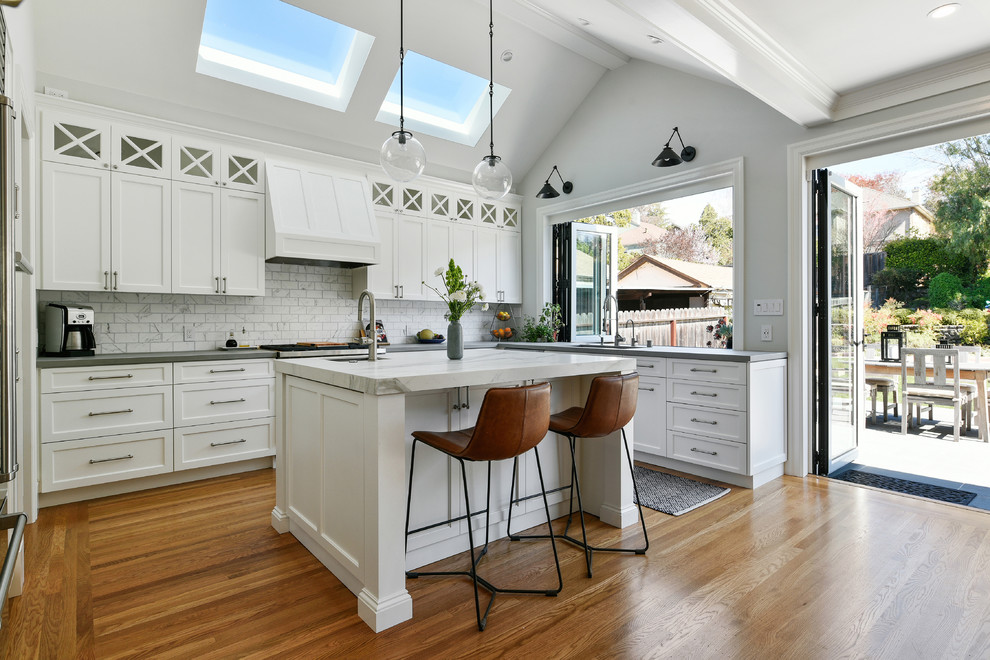 Example of a mid-sized transitional u-shaped medium tone wood floor and brown floor open concept kitchen design in San Francisco with an undermount sink, shaker cabinets, white cabinets, white backsplash, stainless steel appliances, an island, gray countertops, concrete countertops and marble backsplash