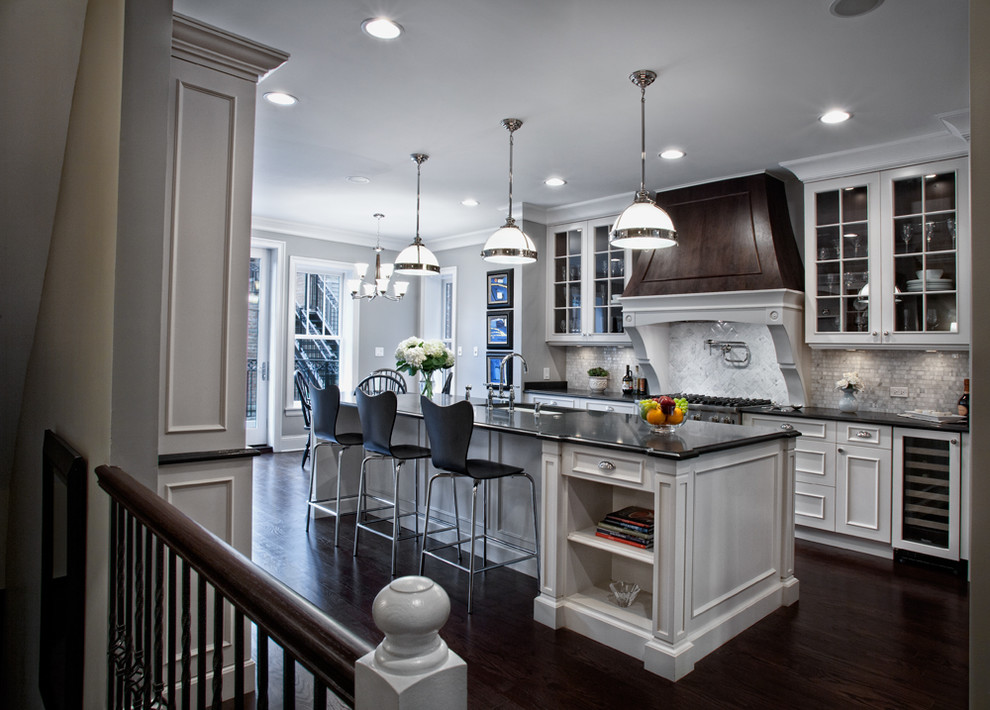 Inspiration for a large timeless galley dark wood floor eat-in kitchen remodel in Chicago with glass-front cabinets, white cabinets, white backsplash, paneled appliances, an undermount sink, granite countertops, stone tile backsplash and an island