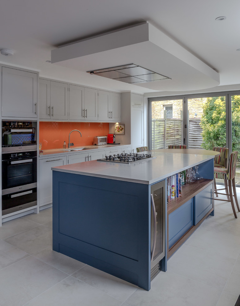Eat-in kitchen - transitional galley gray floor eat-in kitchen idea in London with shaker cabinets, gray cabinets, orange backsplash, black appliances and an island