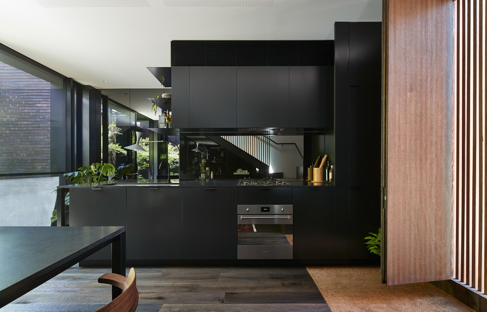 Design ideas for a contemporary eat-in kitchen in Melbourne with flat-panel cabinets, dark wood cabinets, stainless steel appliances, dark hardwood floors and no island.