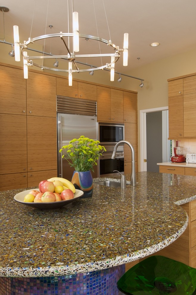 Kitchen - contemporary kitchen idea in Seattle with recycled glass countertops, an undermount sink, flat-panel cabinets, medium tone wood cabinets and stainless steel appliances