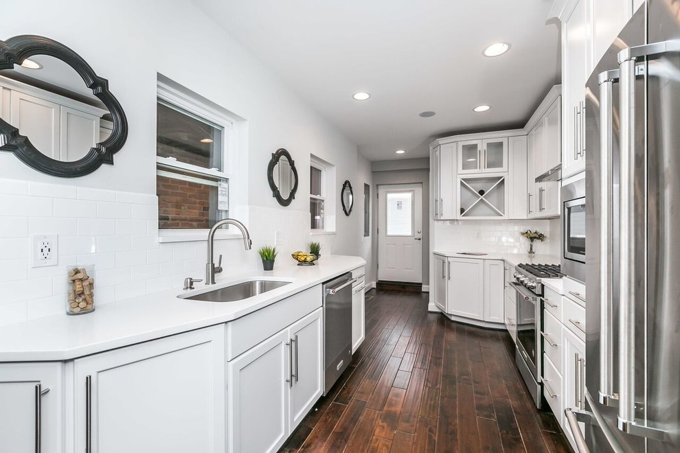 Inspiration for a mid-sized cottage galley dark wood floor and brown floor enclosed kitchen remodel in Baltimore with an undermount sink, shaker cabinets, white cabinets, solid surface countertops, white backsplash, subway tile backsplash, stainless steel appliances, no island and white countertops