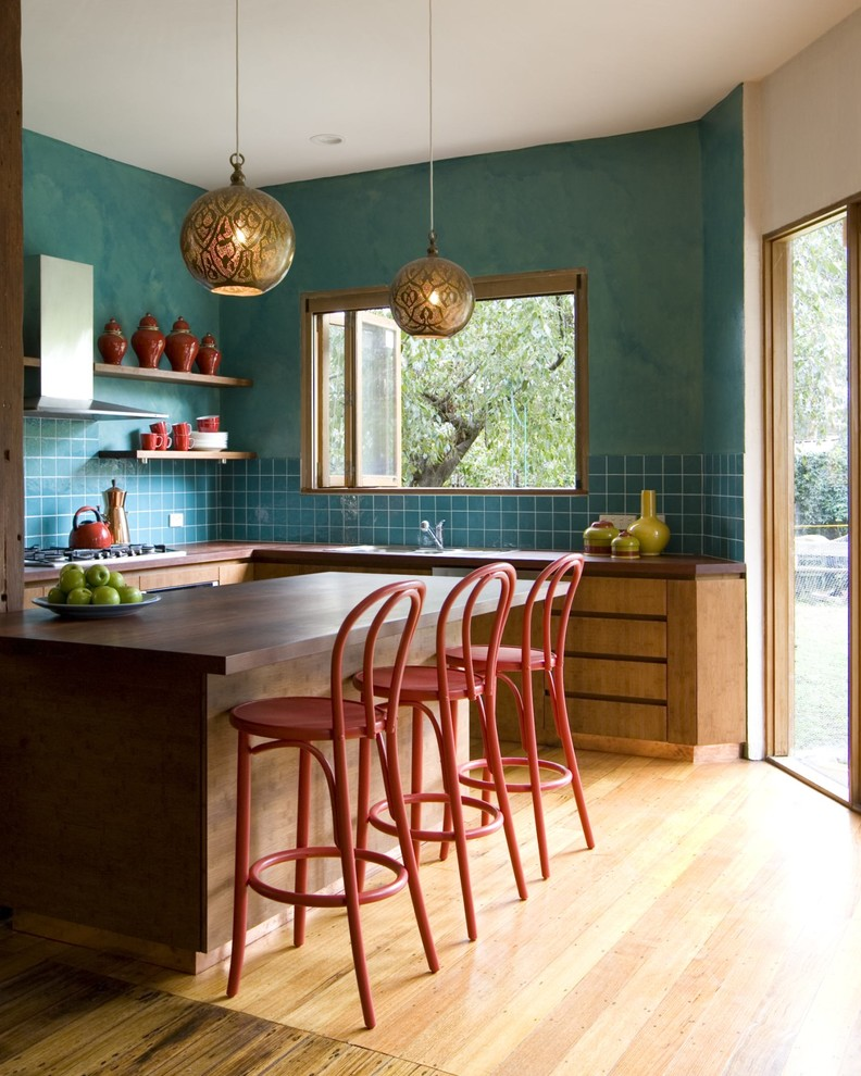 Large transitional u-shaped light wood floor eat-in kitchen photo in Melbourne with flat-panel cabinets, medium tone wood cabinets, blue backsplash, an undermount sink, wood countertops, ceramic backsplash, stainless steel appliances and an island