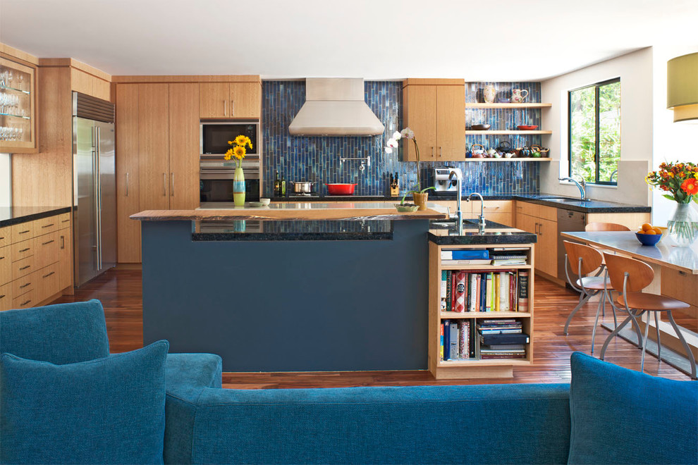 Trendy open concept kitchen photo in Los Angeles with stainless steel appliances, wood countertops, flat-panel cabinets, light wood cabinets and blue backsplash