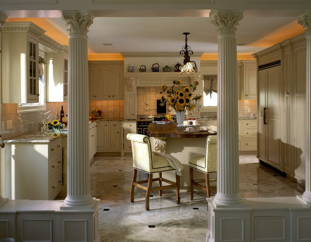 Kitchen - large traditional u-shaped marble floor kitchen idea in New York with beaded inset cabinets, yellow cabinets, black appliances, a farmhouse sink, wood countertops, ceramic backsplash and an island