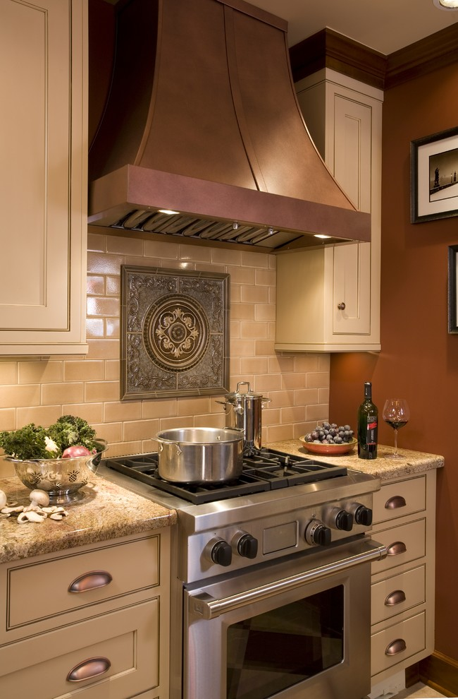 Kitchen - traditional kitchen idea in Portland with stainless steel appliances, granite countertops, beige cabinets, brown backsplash and subway tile backsplash