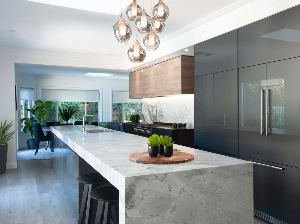 Large trendy galley medium tone wood floor and gray floor open concept kitchen photo in Sydney with a drop-in sink, marble countertops, stone slab backsplash, black appliances, an island, flat-panel cabinets, brown cabinets, gray backsplash and gray countertops