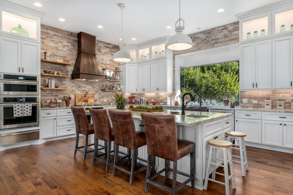 Example of a transitional u-shaped medium tone wood floor and brown floor kitchen design in Austin with a farmhouse sink, recessed-panel cabinets, white cabinets, granite countertops, multicolored backsplash, stone tile backsplash, stainless steel appliances, an island and beige countertops