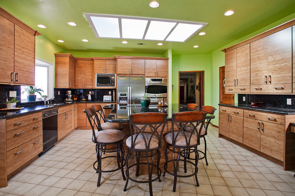 Example of a minimalist u-shaped eat-in kitchen design in San Diego with a drop-in sink, flat-panel cabinets, light wood cabinets, granite countertops, multicolored backsplash, stone slab backsplash and stainless steel appliances