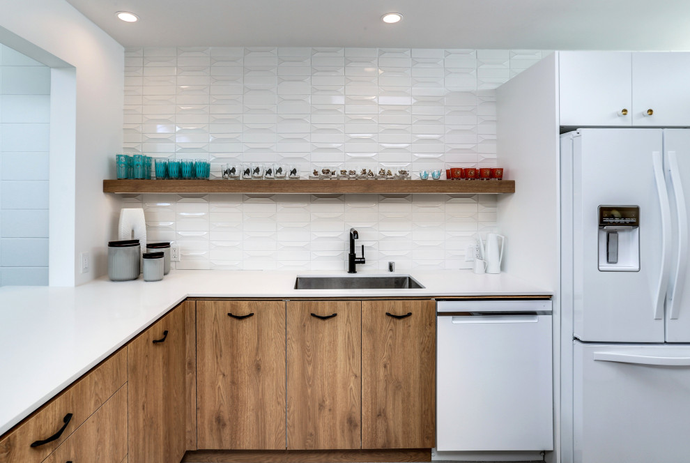 Inspiration for a mid-sized mid-century modern l-shaped kitchen remodel in Other with an undermount sink, flat-panel cabinets, medium tone wood cabinets, white backsplash, glass tile backsplash, a peninsula and white countertops