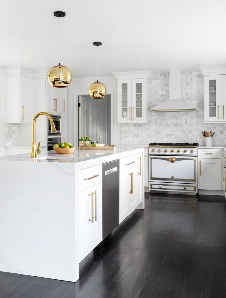 Example of a transitional dark wood floor and black floor kitchen design in New York with an undermount sink, shaker cabinets, white cabinets, white backsplash, marble backsplash, white appliances, an island and white countertops