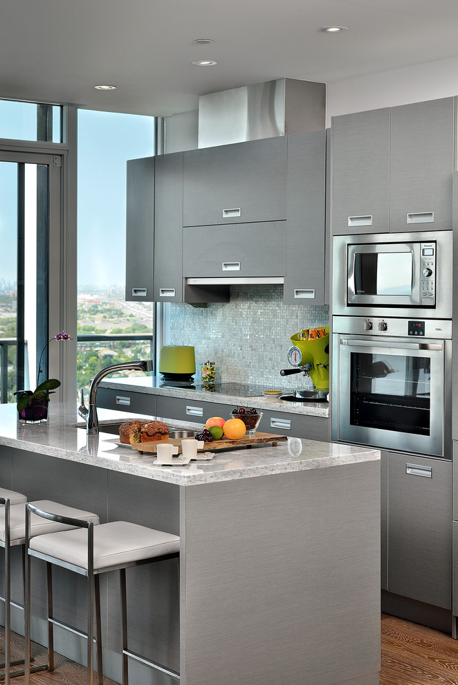 Example of a trendy galley kitchen design in Toronto with marble countertops, stainless steel appliances, flat-panel cabinets and gray cabinets