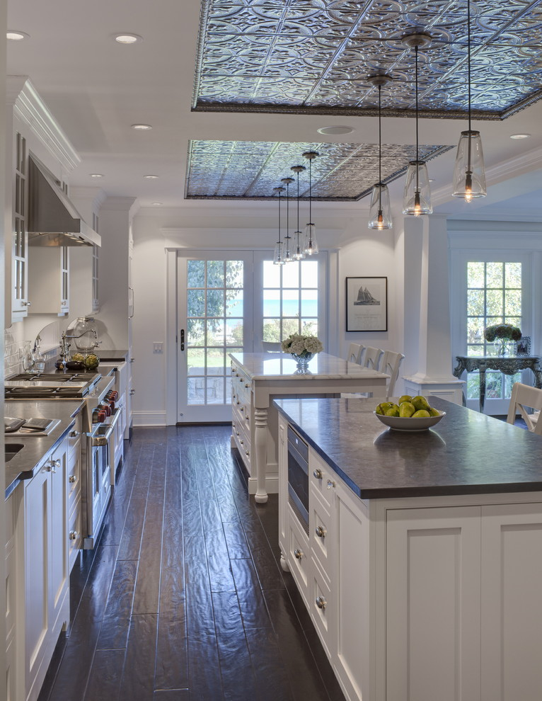 Kitchen - traditional kitchen idea in Chicago with recessed-panel cabinets, white cabinets, two islands and black countertops