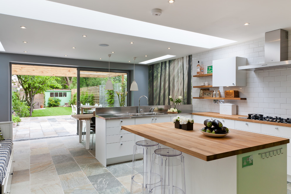 This is an example of a medium sized contemporary kitchen/diner in Other with an integrated sink, flat-panel cabinets, white cabinets, wood worktops, white splashback, an island and metro tiled splashback.