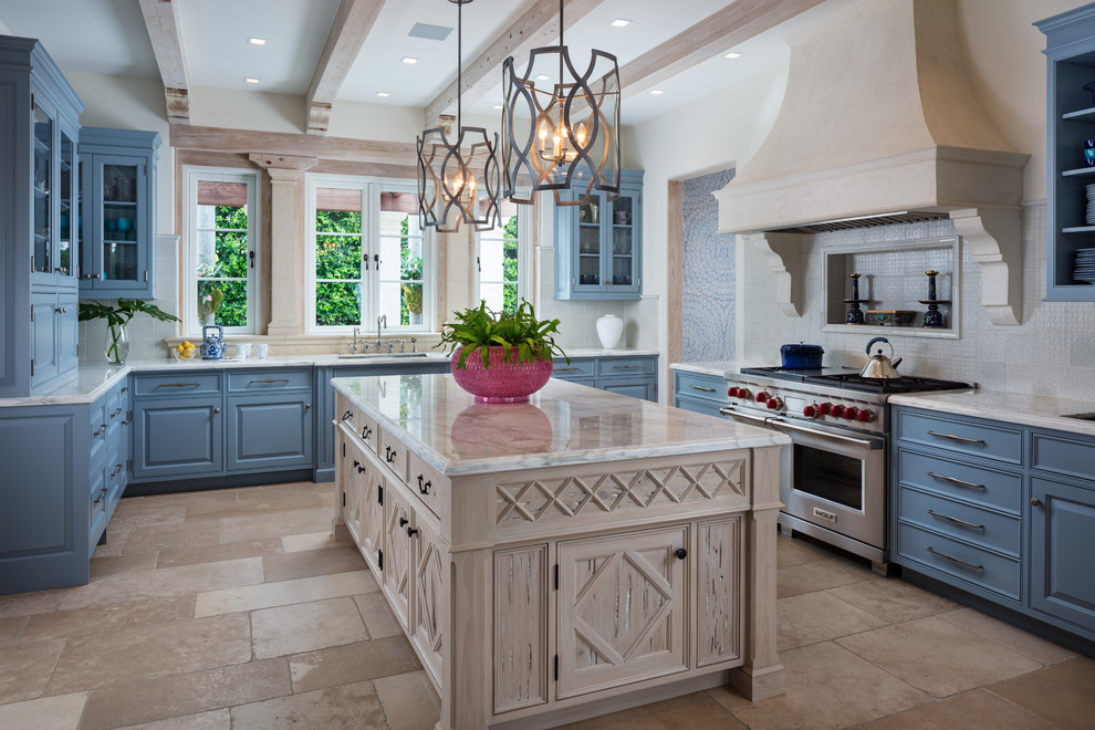 Inspiration for a mediterranean u-shaped beige floor kitchen remodel in Miami with an undermount sink, raised-panel cabinets, blue cabinets, stainless steel appliances, an island and white countertops