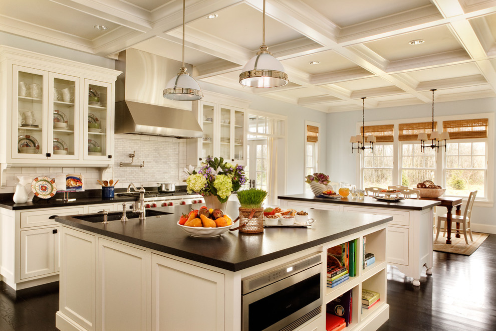 Eat-in kitchen - large traditional dark wood floor eat-in kitchen idea in Portland with stainless steel appliances, recessed-panel cabinets, white cabinets, white backsplash, subway tile backsplash, granite countertops, an undermount sink, two islands and black countertops