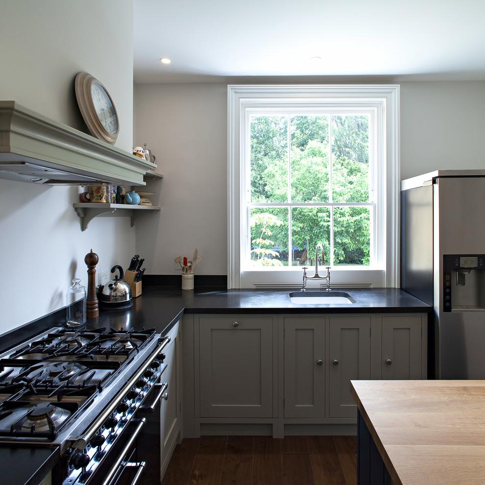 ロンドンの中くらいのヴィクトリアン調のおしゃれなキッチン (エプロンフロントシンク、シェーカースタイル扉のキャビネット、緑のキャビネット、御影石カウンター、黒い調理設備、濃色無垢フローリング、黒いキッチンパネル) の写真